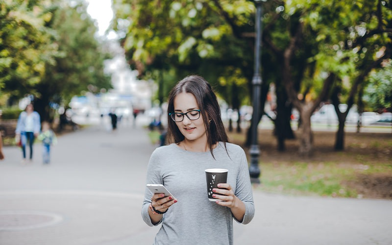 A Women walking in a park with her coffee.