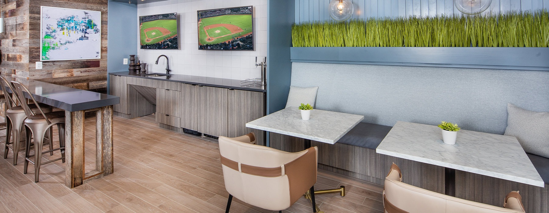Large clubroom with wood floors and plenty of seating and multiple TV's