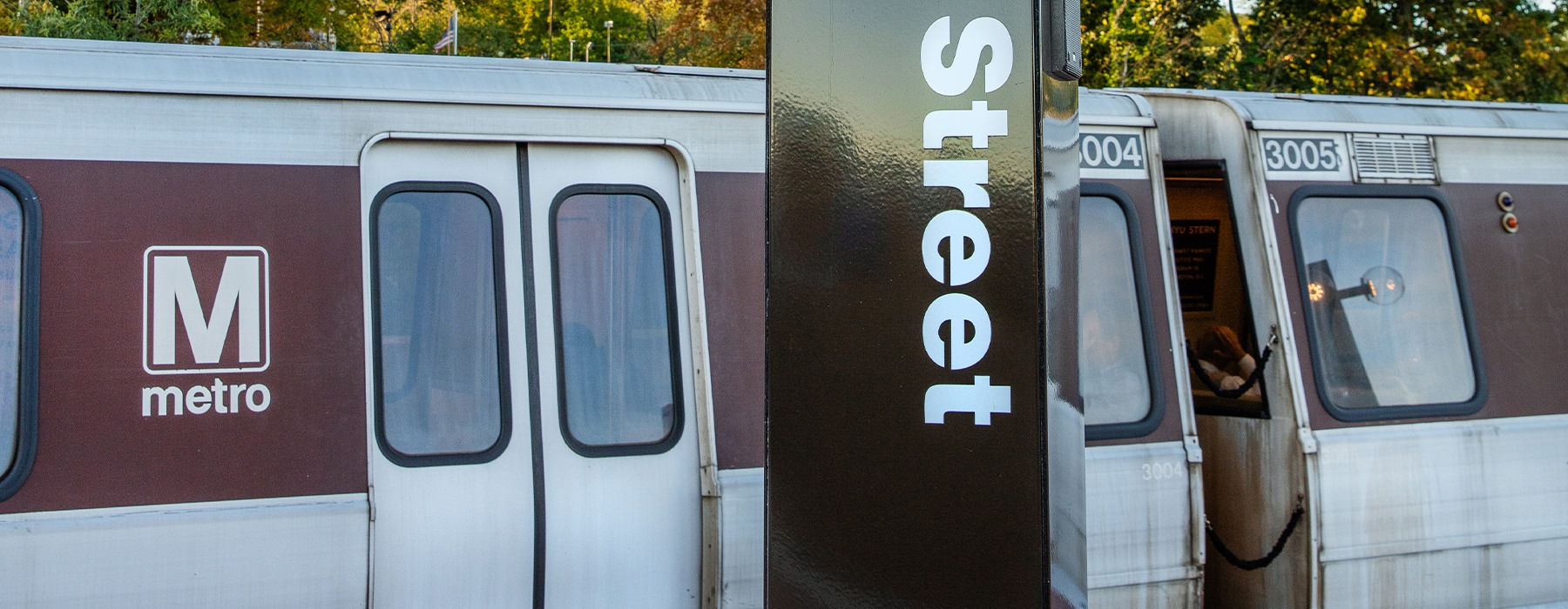 A metro rail car is parked at the terminal waiting for passengers.