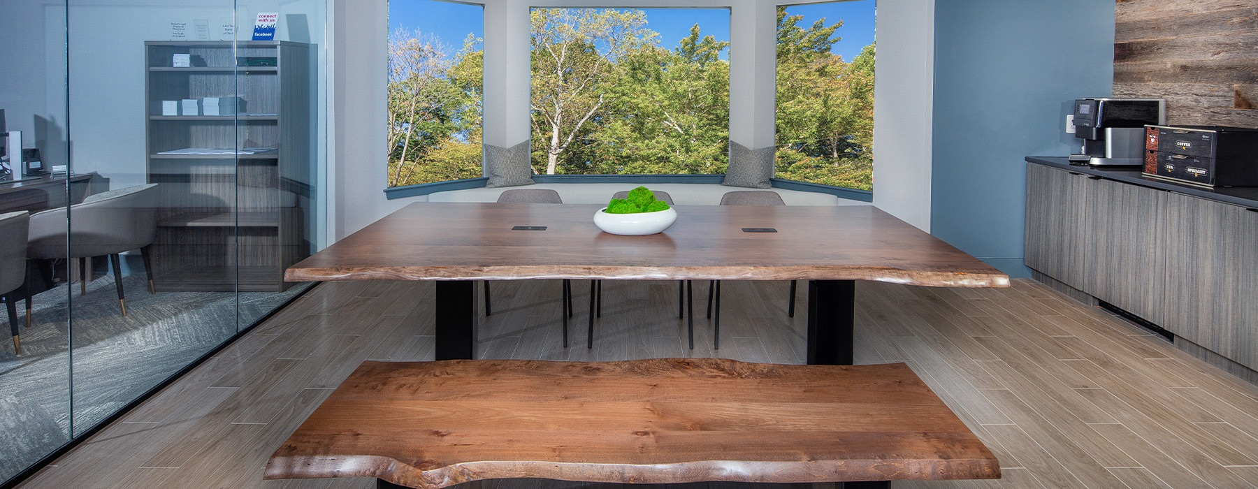 Spacious community kitchen with rustic style wood table and large windows with a view.